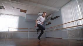 Молодой студент танцев школы танцев в классе Он показывая современный танец бедр-хмеля в бальном зале красивейший человек видеоматериал