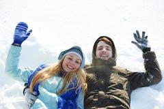 Молодой счастливый лежать на снеге в зиме Стоковые Изображения RF