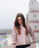 Молодой счастливый портрет женщины, смотря вниз и усмехаясь, одел в милом нежном розовом свитере, моде осени стоковая фотография rf