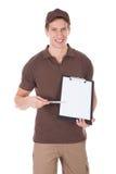 Молодой счастливый работник доставляющий покупки на дом показывая форму на доске сзажимом для бумаги стоковые изображения