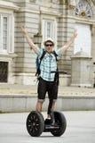 Молодой счастливый туристский человек с путешествием города катания рюкзака segway управляющ счастливым и excited посещая дворцом Стоковые Фото