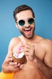 Молодой счастливый человек держа коктеиль от кокосов Стоковая Фотография