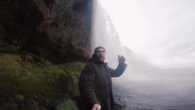 Молодой счастливый человек с киносъемкой ручки selfie на водопаде Seljalandsfoss камеры gopro мощном в Исландии в туманном дне сток-видео