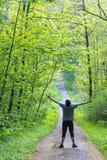 Молодой счастливый человек с оружиями протянул наслаждаться жизнью в лесе стоковое фото rf