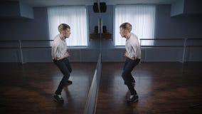 Молодой танцор хонингует движения стоя перед большим зеркалом в студии танца Хорошо прорепетированный тазобедренный танец хмеля с акции видеоматериалы