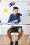 Молодой творческий дизайнерский человек работая на офисе. Стоковая Фотография RF