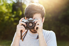 Молодой творческий фотограф делая фото при ретро камера, фотографируя красивые ландшафты природы пока отдыхающ на зеленом f Стоковая Фотография