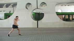 Молодой топлесс кавказский человек в шортах бокс тени на предпосылке конкретной серой стены с круговым отверстием акции видеоматериалы