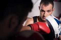 Молодой тренер держа пусковую площадку бокса Стоковые Изображения