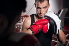 Молодой тренер держа пусковую площадку бокса Стоковые Фото