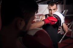 Молодой тренер держа пусковую площадку бокса Стоковое фото RF