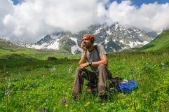 Молодой туристский отдыхать на верхней части обозревая долину Стоковые Изображения RF