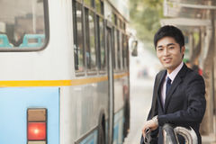 Молодой, уверенно бизнесмен ждать на автобусной остановке для шины в Пекине, Китая Стоковые Изображения