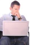 Молодой уверенно бизнесмен проверяя почту на его тетради и думать стоковая фотография