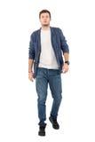 Молодой уверенно человек в джинсовой ткани unbuttoned рубашка и джинсы идя к камере стоковое фото