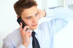 Молодой усмехаясь бизнесмен говоря на сотовом телефоне Стоковое Фото