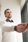 Молодой усмехаясь бизнесмен тряся женскую руку стоя в офисе Стоковая Фотография RF