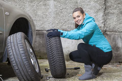 Молодой усмехаясь водитель женщины заменяя автошины Стоковая Фотография