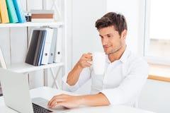 Молодой усмехаясь кофе бизнесмена выпивая и печатать на компьтер-книжке Стоковая Фотография