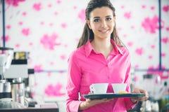 Молодой усмехаясь кофе сервировки официантки на баре Стоковые Изображения RF