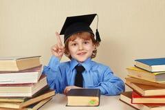 Молодой усмехаясь мальчик в академичной шляпе среди старых книг стоковая фотография