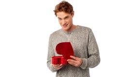 Молодой усмехаясь парень держа подарочную коробку стоковая фотография rf