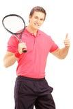 Молодой усмехаясь человек держа ракетку тенниса и давая большой палец руки вверх Стоковая Фотография