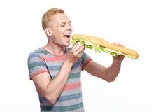 Молодой усмехаясь человек начиная съесть длинный сандвич стоковые фотографии rf