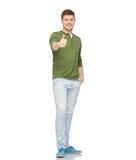 Молодой усмехаясь человек показывая большие пальцы руки вверх над белизной Стоковая Фотография