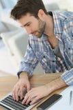 Молодой усмехаясь человек работая на компьтер-книжке Стоковые Фото