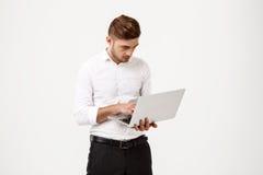 Молодой успешный бизнесмен печатая на компьтер-книжке над белой предпосылкой Стоковое фото RF