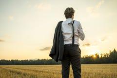 Молодой успешный бизнесмен стоя в пшеничном поле смотря gaz Стоковые Изображения