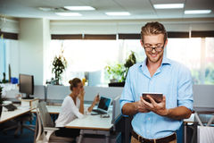 Молодой успешный усмехаться бизнесмена, смотря таблетку, над предпосылкой офиса Стоковая Фотография RF