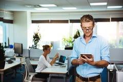 Молодой успешный усмехаться бизнесмена, смотря таблетку, над предпосылкой офиса Стоковое фото RF