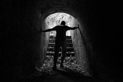 Молодой утомленный человек выходит темный каменный тоннель Стоковое Фото