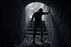 Молодой утомленный человек выходит темный каменный тоннель Стоковое фото RF