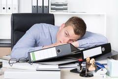 Молодой утомленный человек лежит на столе в офисе стоковая фотография