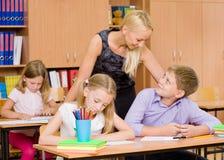 Молодой учитель наблюдает студентов во время экзамена стоковое изображение rf