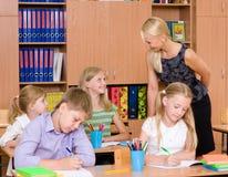 Молодой учитель помогает студентам начальной школы в экзамене стоковая фотография