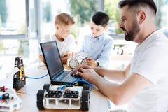 Молодой учитель робототехники работая на компьтер-книжке Стоковая Фотография RF