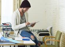 Молодой ультрамодный бизнесмен в взгляде beanie и холодного битника неофициальном сидя на столе домашнего офиса используя цифрову стоковые фотографии rf