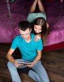 Молодой ходить по магазинам пар онлайн используя цифровой планшет Соедините смеяться над, девушку лежа на кровати дома и парня Стоковое Фото