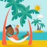 Молодой чернокожий человек на пляже th ослабляя и выпивая Стоковое Фото