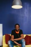 Молодой чернокожий человек сидит на кресле с наушниками стоковое изображение rf