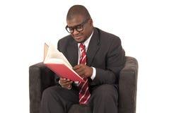 Молодой чернокожий человек сидя в стуле читая книгу стоковое изображение rf