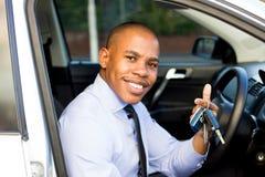 Молодой чернокожий человек усмехаясь пока сидящ в его автомобиле Стоковая Фотография RF