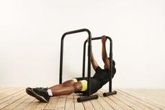 Молодой черный спортсмен делая bodyweight гребет на передвижных барах стоковое изображение rf