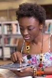 Молодой черный студент используя ее таблетку, изучая Стоковые Фото