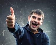 Молодой человек давая большой палец руки вверх Стоковое Изображение