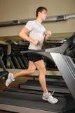 Молодой человек бежать на третбане в спортзале Стоковое фото RF